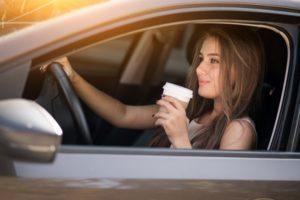 girl getting coffee in a car