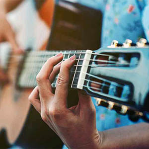 Close up images of woman's hands playing acoustic guitar IN BLAINE