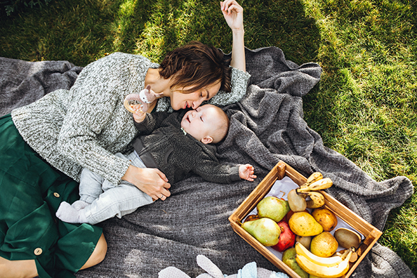 Mother with her little son having picnic on a back yard in Blaine's Park