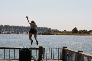 girl jumping in from the Jorgensen Pier