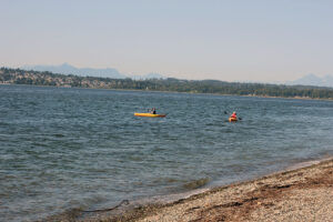 two kayakers paddle through the waters of Semiahmoo sea in Blaine overseeing White Rock