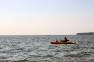 a kayaker paddles through the waters of Semiahmoo sea in Blaine overseeing White Rock